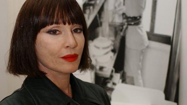 Die Künstlerin Manon posiert vor einem Bild in ihrer Ausstellung.