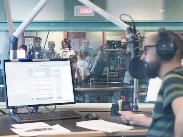 Moderator im Studio, im Hintergrund durch Scheibe abgetrennt das Publikum im Regieraum