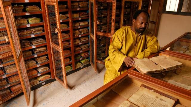 Ein schwarzer Mann in gelbem Kleid sitzt in einer Bibliothek, vor ihm ein altes Manuskript.