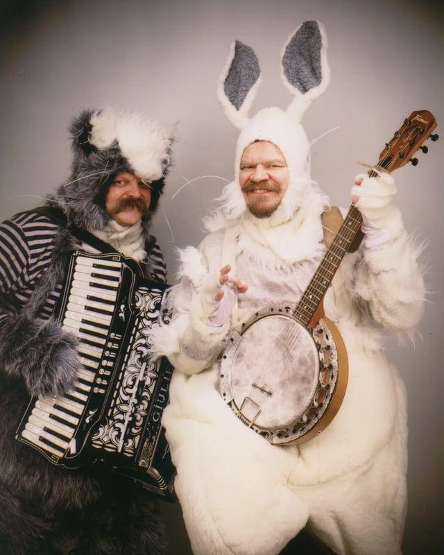 Zwei Männer in Tierkostümen  mit Harmonika und Banjo.