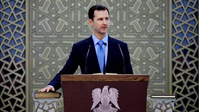 Assad an einem Rednerpult.