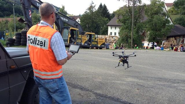 Baselbieter Polizist mit Warnweste bedient Fernsteuerung, im Hintergrund hebt die Drohne ab.