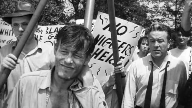 Filmstill: Ein Mann mit offenem Hemd steht vor Demonstranten, die rassistische Parolen auf Plakate geschmiert haben.