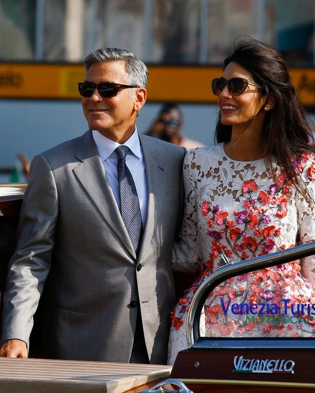 George Clooney und seine Frau posieren auf einem Boot.