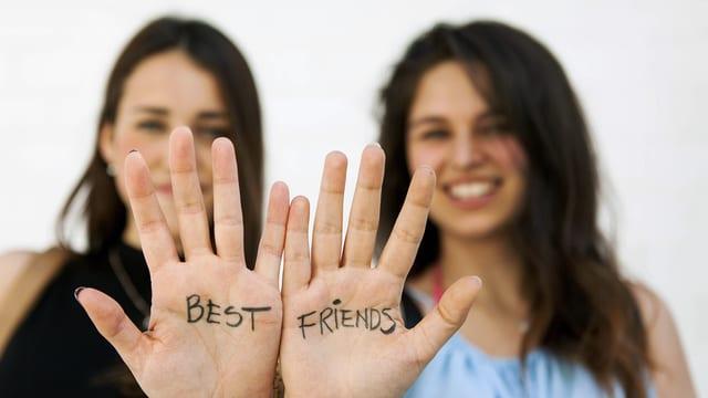 Zwei Mädchen halten ihre Hände in die Kamera. Darauf steht: Best Friends.