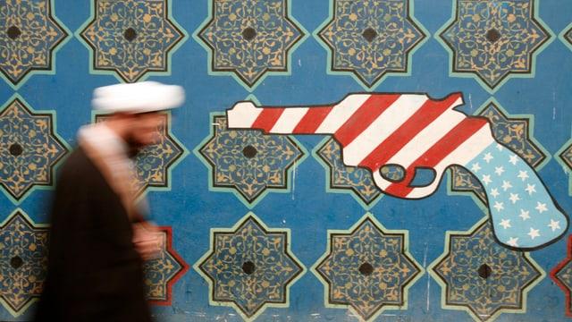 Kleriker läuft an Graffti vorbei, das Pistole mit US-Farben zeigt