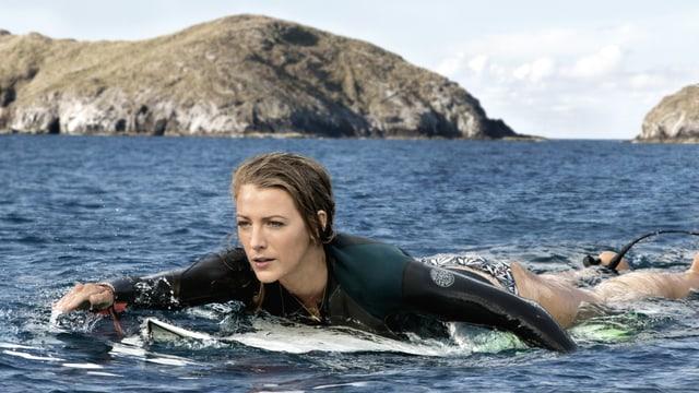 Eine junge Frau paddelnd auf einem Surfbrett.