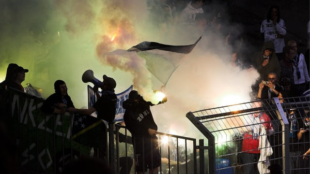 Publikum im Stadion, Rauchpetarden, eine Fahne.