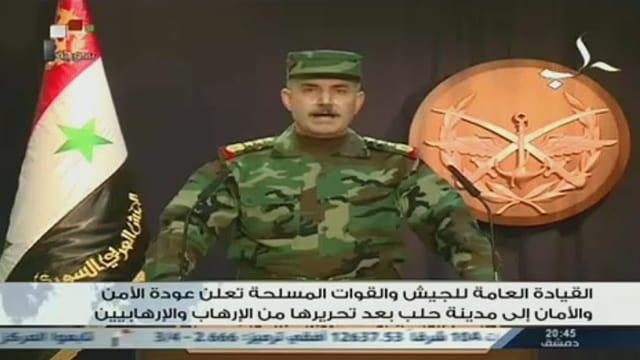 Ein Offizier in Uniform vor der syrischen Flagge und dem Emblem der syrischen Armee.