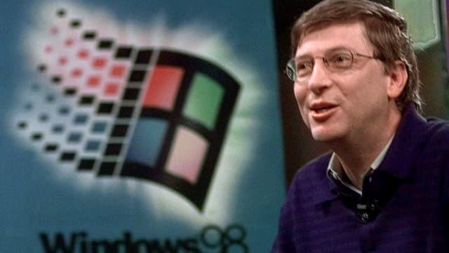 Bill Gates Gates vor einem Windows 98 Logo