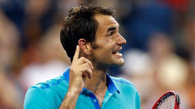 Roger Federer hebt seinen Zeigefinger ans Ohr.