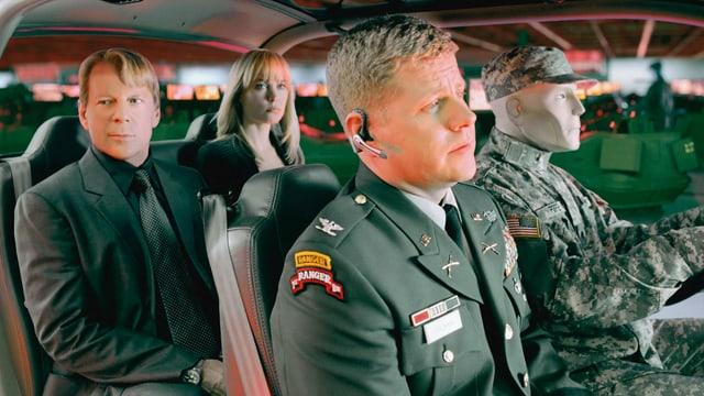 Zwei Männer, eine Frau und eine Puppe sitzen in einem Fahrzeug. Ein Mann und die Puppe tragen Militäruniformen.