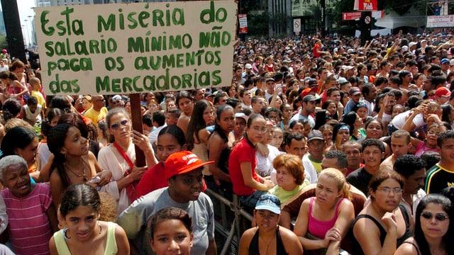 Demonstration. Viele Menschen, eine Frau schwenkt eine Plakat mit Forderungen in die Höhe.