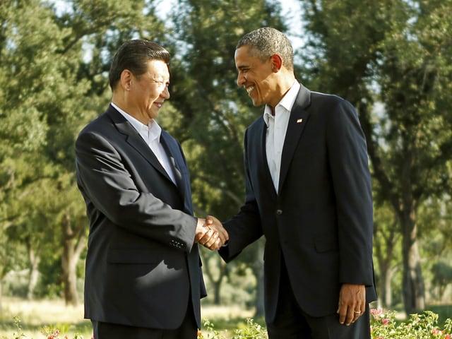 Chinas Präsident Xi Jinping und US-Präsident Barack Obama schütteln einander die Hände und lächeln – ohne Krawatten. (reuters)