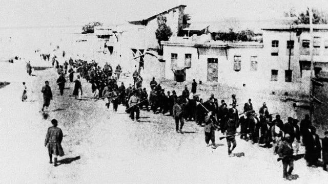 Schwarz-weiss-Aufnahme: Eine Reihe Menschen geht durch ein Dorf, bewacht von bewaffneten Männern.