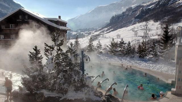 Ein Thermalbad im Winter, dahinter schneebedeckte Hänge.
