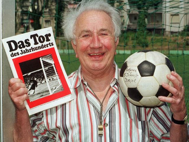 Gottfried Dienst hält einen Ball und eine Zeitschrift in die Kamera.
