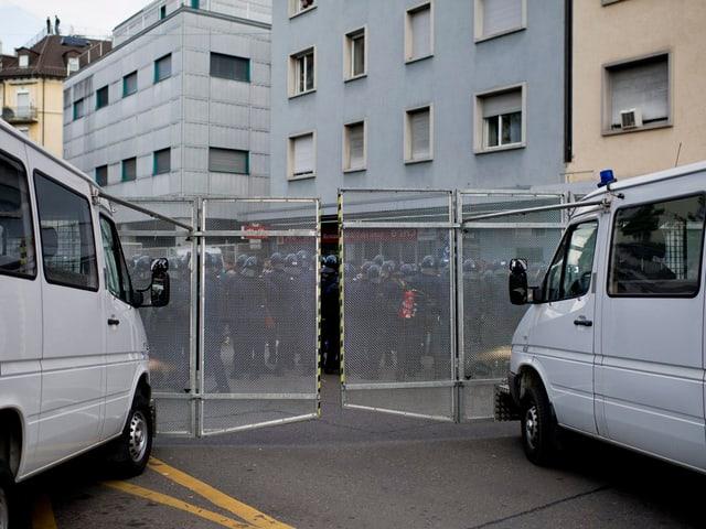 Zwei graue Polizeikastenwagen und mehrere Polizisten in Kampfmontur plus zwei Gitter
