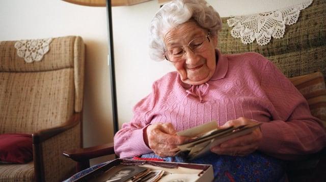 Eine betagte Frau im Sessel sortiert Fotos.