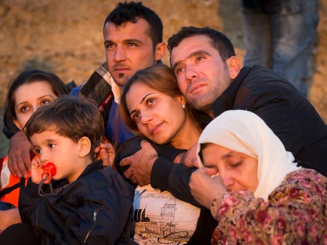 Eine Familie liegt sich nach der Ankunft auf Kos in den Armen.