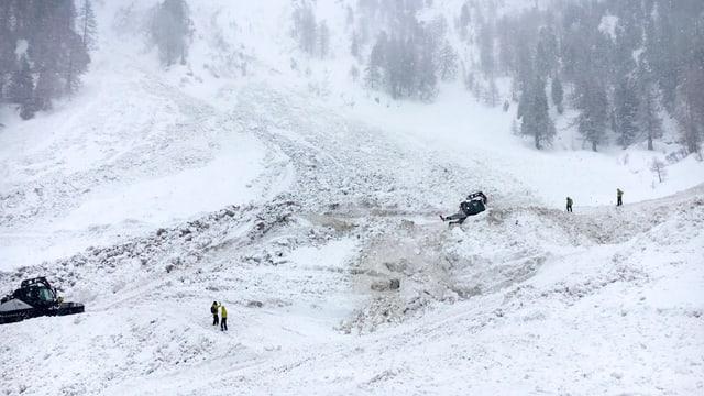 Rettungskräfte suchen nach den verschütteten Skifahrern.