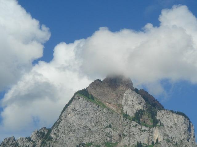 Berggipfel im Sommer mit eine Wolke ganz oben. Die Blumenkohlwolken beginnt auf Gipfelhöhe und wächst in den Himmel.