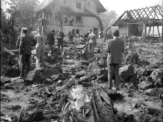 Männer, die inmitten von Trümmerteilen stehen.