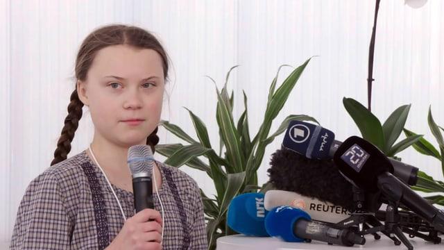 Eine Jugendliche hält ein Mikrofon, neben ihr sind weitere Mikrofone