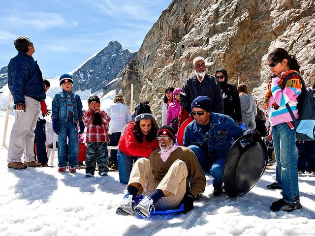 Eine Gruppe indischer Touristen macht sich bereit für eine Rodelfahrt