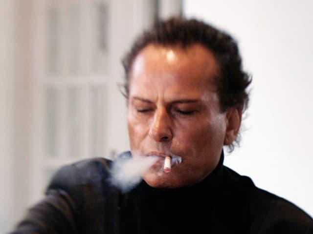 Hans Barlach sitzt mit einem Kaffe an einem Tisch und raucht eine Zigarette.
