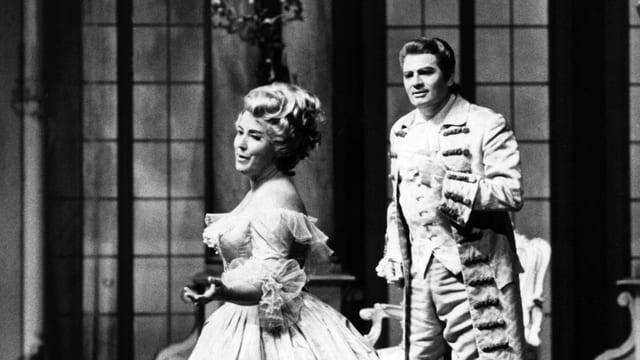 Auf einer Opernbühne: eine Frau und ein Mann sind pompös gekleidet und frisiert. Sie singen.