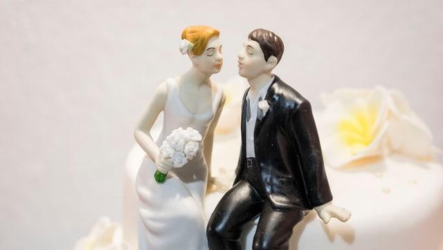 Ein kleines Hochzeitspaar aus Plastik sitzt auf einer Hochzeitstorte.