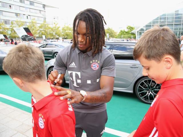 Renato Sanches gibt einem Jungen ein Autogramm aufs Shirt