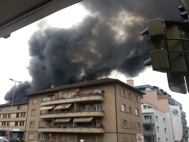Schwarzer Rauch steigt hinter Häusern auf.