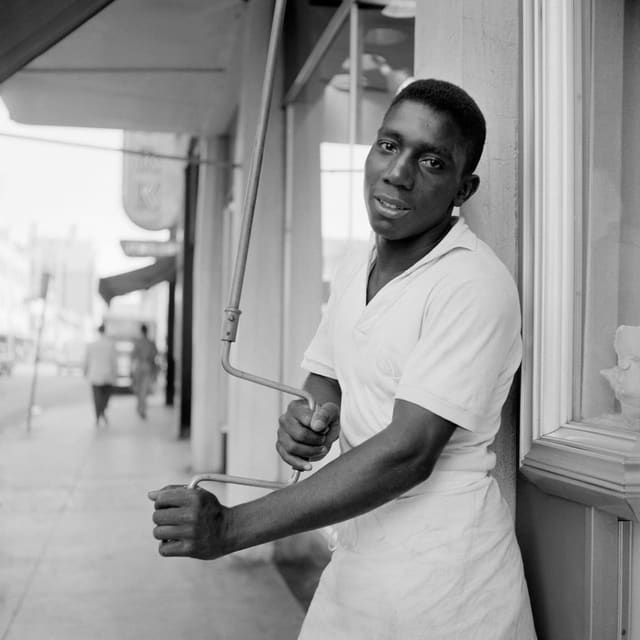 Ein schwarzer Mann hält eine Kurbel in der Hand.