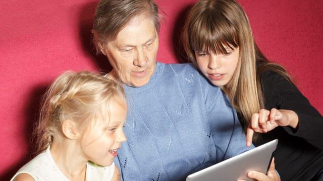 Eine ältere Frau spielt mit zwei Kindern am Tablet.