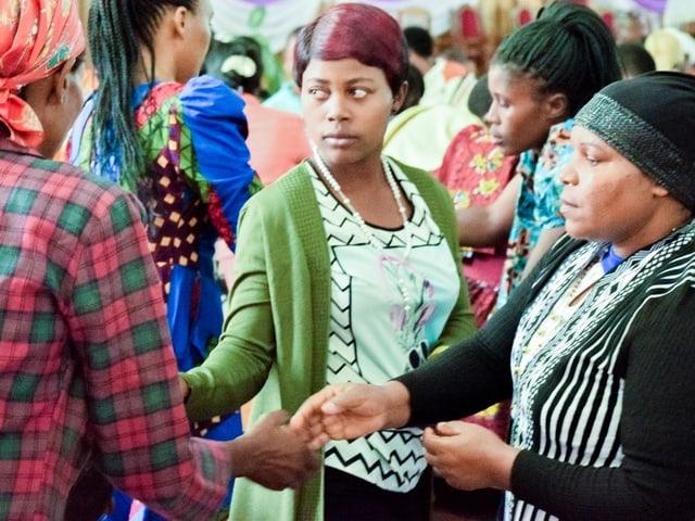 Drei Frauen halten Hände.