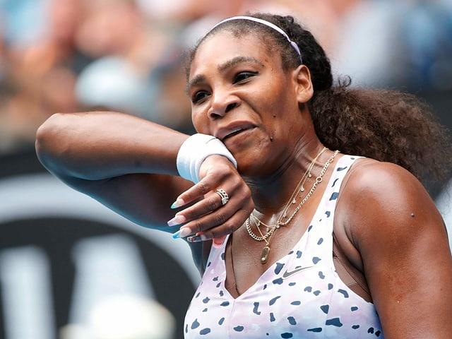 Serena Williams wischt sich mit der rechten Hand übers Gesicht.