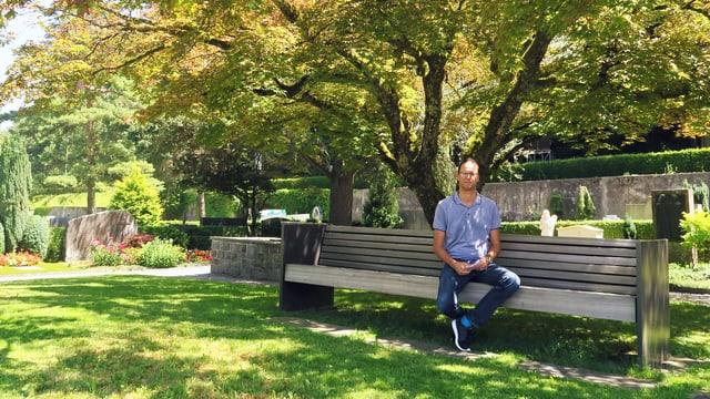 Mann auf einer Bank vor einem Baum an einem sonnigen Tag. Links im Bild 2 Grabsteine.