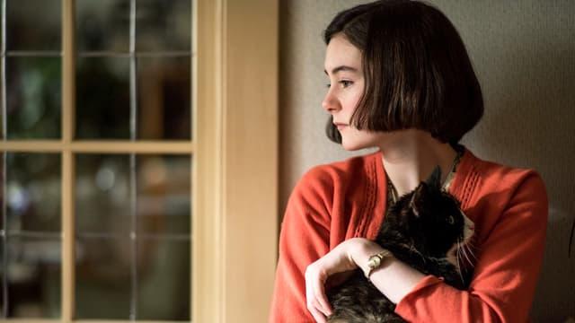 Ein Mädchen mit Pagenschnitt steht am Fenster und trägt eine Katze auf ihrem Arm.