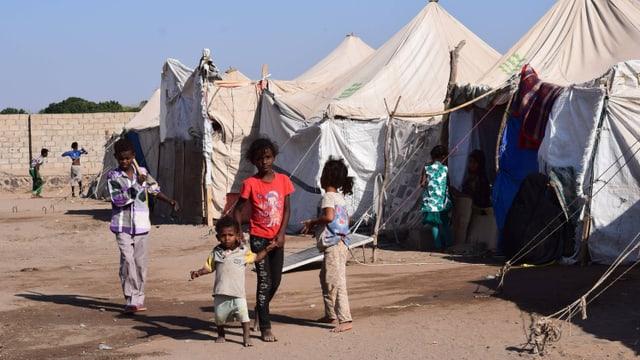Kinder vor Zelten in einem Flüchtlingslager.