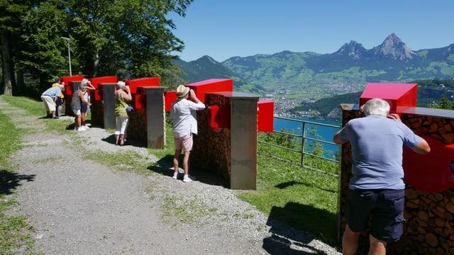 Touristen betrachten an einem Themenposten die Bergwelt um den Vierwaldstättersee.