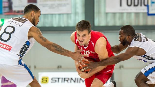 Ein Basketballspieler von Swiss Central Basket schirmt den Ball gegen zwei Fribourgspieler