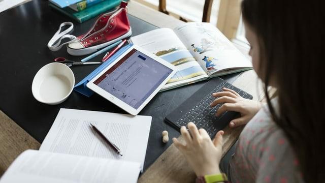 ein Mädchen schreibt ihre Hausaufgaben am Tablet
