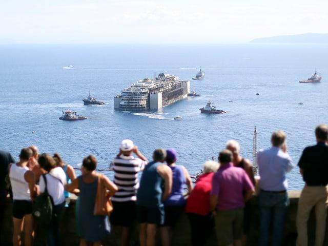Touristen beäugen die Einfahrt der Costa Concordia.