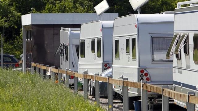 Wohnwagen stehen auf dem Durchgangsplatz für Fahrende im Aarauer Schachen. Im Hintergrund sanitäre Einrichtungen.