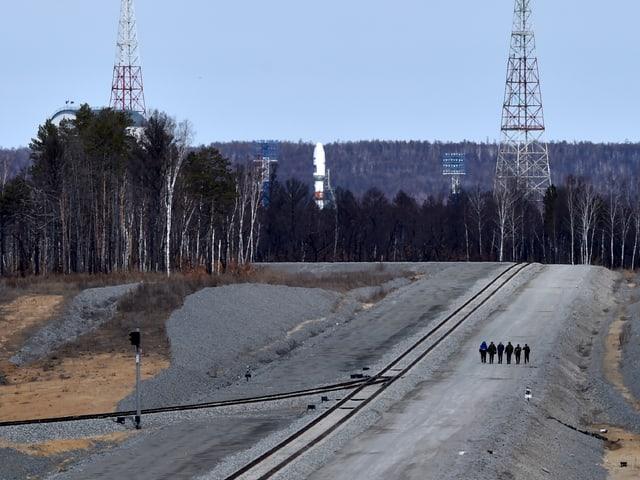 Das Bild zeigt weit hinten den oberen Teil der Rakete. Rundum hat es karge Bäume und Kiesstrassen