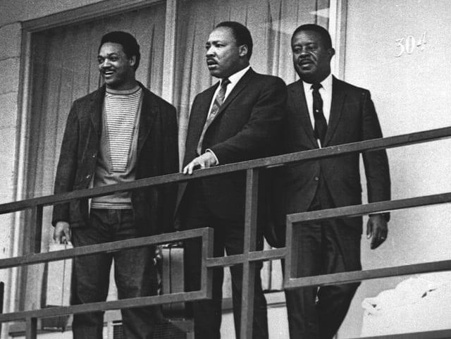 Drei Männer in Anzügen stehen auf einem Balkon