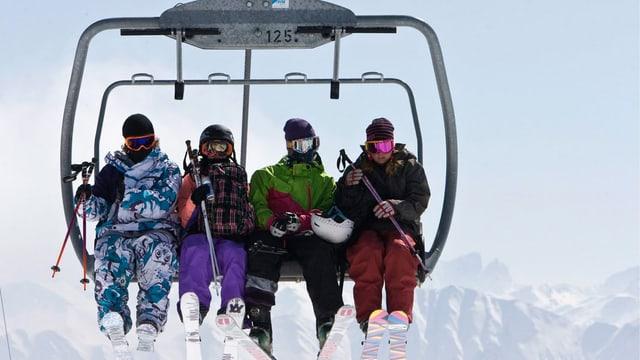Vier Skifahrer auf einem Sessellift.