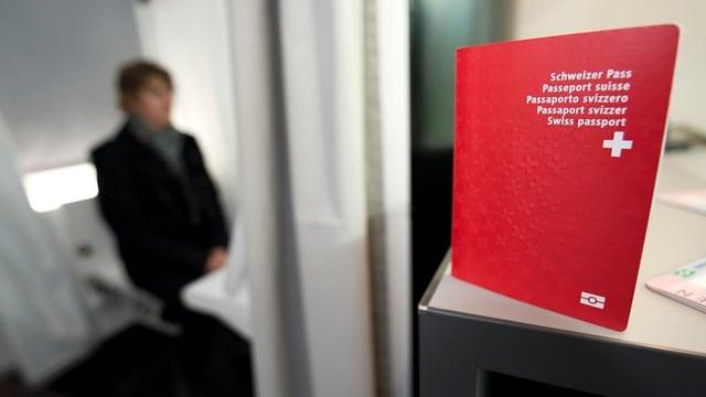 Ein Schweizer Pass im Vordergrund. Einen Person im Hintergrund sitzt im Passfotoautomat.